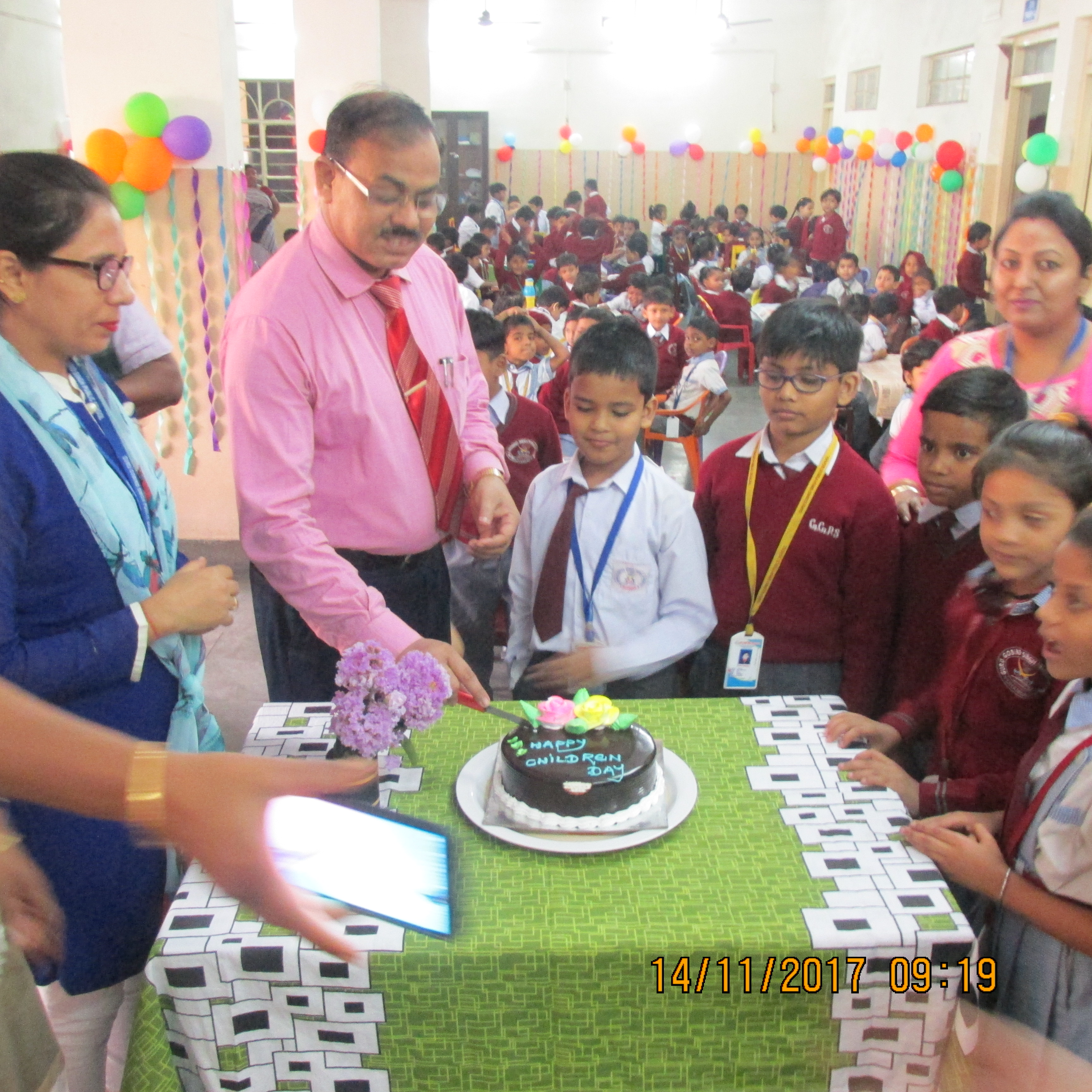 Principal Sir helping the child to cut cake